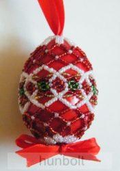Piros színű, gyöngyökkel díszített műanyag tojás